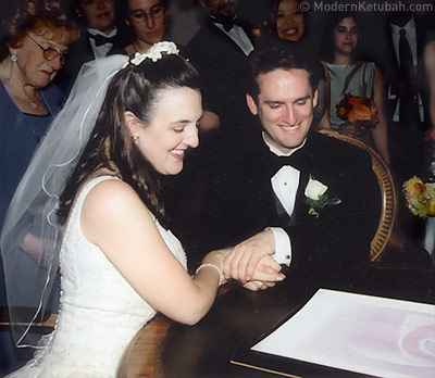 Daniel Sroka of Modern Ketubah and his wife signing the ketubah he made for their wedding.